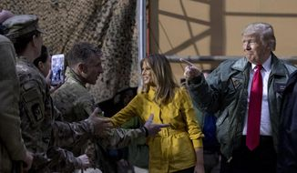 President Donald Trump and first lady Melania Trump greet members of the military as they arrive for a hanger rally at Al Asad Air Base, Iraq, Wednesday, Dec. 26, 2018. In a surprise trip to Iraq, President Donald Trump on Wednesday defended his decision to withdraw U.S. forces from Syria where they have been helping battle Islamic State militants. (AP Photo/Andrew Harnik)