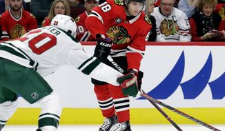 Chicago Blackhawks right wing Patrick Kane, right, looks to pass against Minnesota Wild defenseman Ryan Suter during the first period of an NHL hockey game Thursday, Dec. 27, 2018, in Chicago. (AP Photo/Nam Y. Huh)