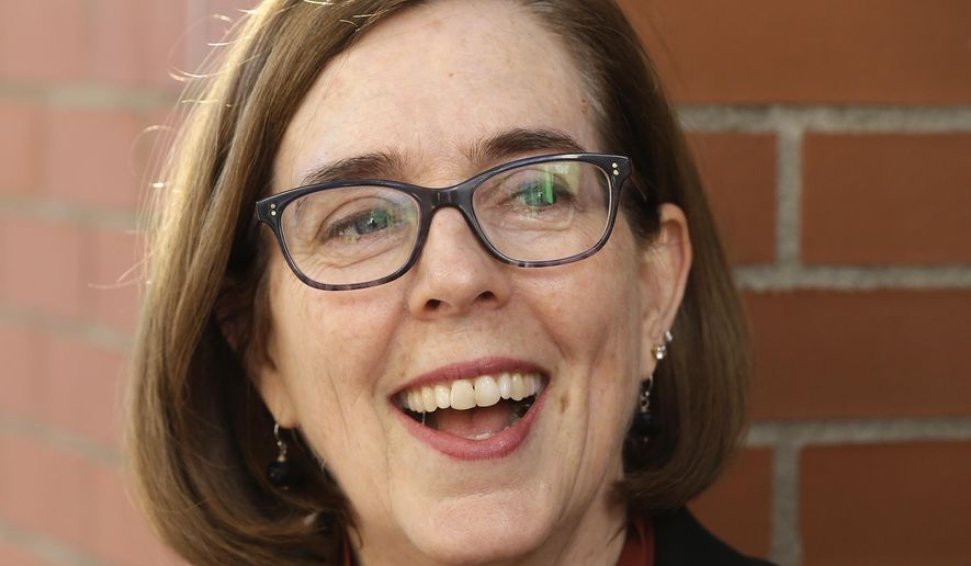 FILE - In this Oct. 17, 2018 file photo, Oregon Gov. Kate Brown smiles during an interview in Portland, Ore. Gov. Brown's election to her first full term was voted Oregon's top news story of 2018. (AP Photo/Don Ryan, File)