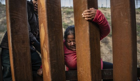 A migrant climbs the border fence before jumping into the U.S. to San Diego, Calif., from Tijuana, Mexico, Thursday, Dec. 27, 2018. Discouraged by the long wait to apply for asylum through official ports of entry, many Central American migrants from recent caravans are choosing to cross the U.S. border wall and hand themselves into border patrol agents. (AP Photo/Daniel Ochoa de Olza)