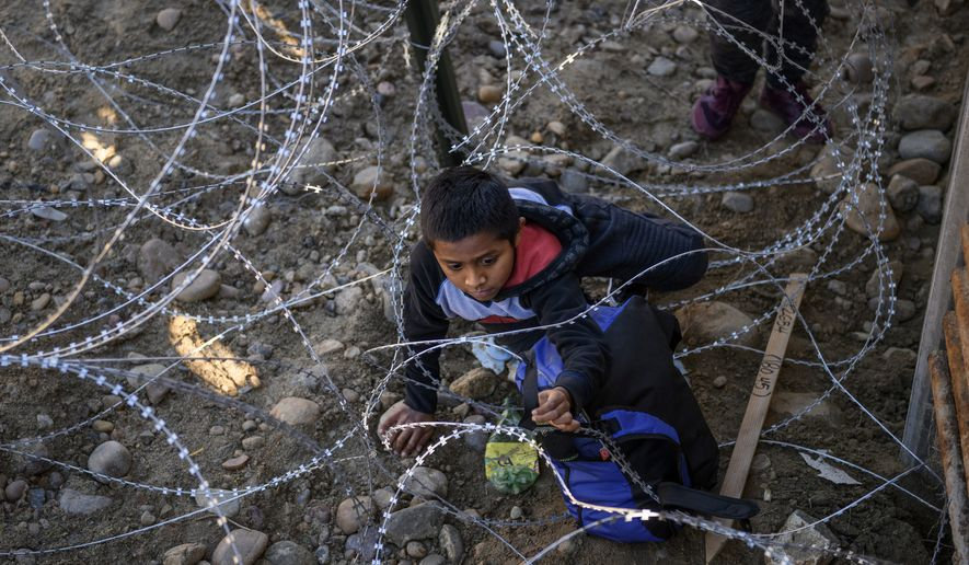 Kevin Andres, a Mexican migrant child from Oaxaca, crawls to get his backpack from the barbed wire after jumping the border fence to get into the U.S. side to San Diego, Calif., from Tijuana, Mexico, Friday, Dec. 28, 2018. Discouraged by the long wait to apply for asylum through official ports of entry, many migrants from recent caravans are choosing to cross the U.S. border wall and hand themselves in to border patrol agents. (AP Photo/Daniel Ochoa de Olza)
