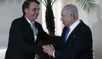 Brazil's President-elect Jair Bolsonaro, left, and Israel's Prime Minister Benjamin Netanyahu shake hands during a joint statement at the military base Fort Copacabana, in Rio de Janeiro, Brazil, Friday, Dec. 28, 2018. Despite earlier reports, Netanyahu plans to attend the inauguration of Bolsonaro on Tuesday,  Jan. 1, 2019 in Brasilia. (Leo Correa/Pool Photo via AP)
