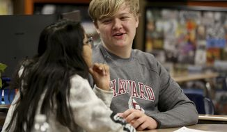 Government class students Alejandra Corral, left, and Braxton Moral work on calculating the estimated cost of living expenses as part of a talk about students who graduate high school making on average more money than non-graduates, at Ulysses High School in Ulysses, Kan., on Wednesday, Dec. 12, 2018. (Sandra J. Milburn/The Hutchinson News via AP)