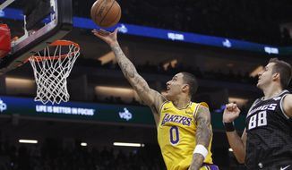 Los Angeles Lakers forward Kyle Kuzma (0) shoots next to Sacramento Kings forward Nemanja Bjelica (88) during the first half of an NBA basketball game in Sacramento, Calif., Thursday, Dec. 27, 2018. (AP Photo/Steve Yeater)