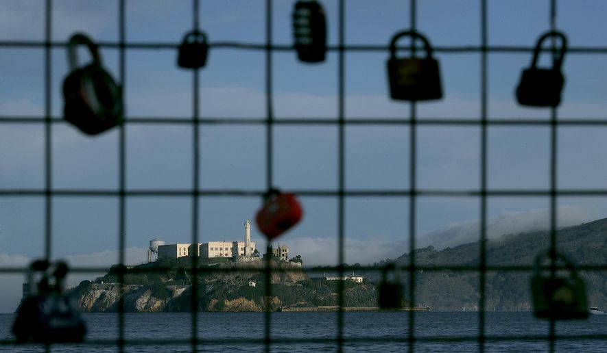 Alcatraz Island is shown behind a locks attached to a pier fence in San Francisco, Saturday, Dec. 22, 2018. A partial federal shutdown has been put in motion because of gridlock in Congress over funding for President Donald Trump's Mexican border wall. The company that provides ferry services to Alcatraz Island kept its daytime tours but canceled behind-the-scenes and night tours. (AP Photo/Jeff Chiu)