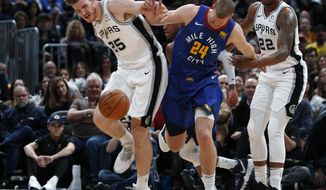 San Antonio Spurs center Jakob Poeltl, left, fights for control of a loose ball with Denver Nuggets forward Mason Plumlee in the first half of an NBA basketball game Friday, Dec. 28, 2018, in Denver. (AP Photo/David Zalubowski)