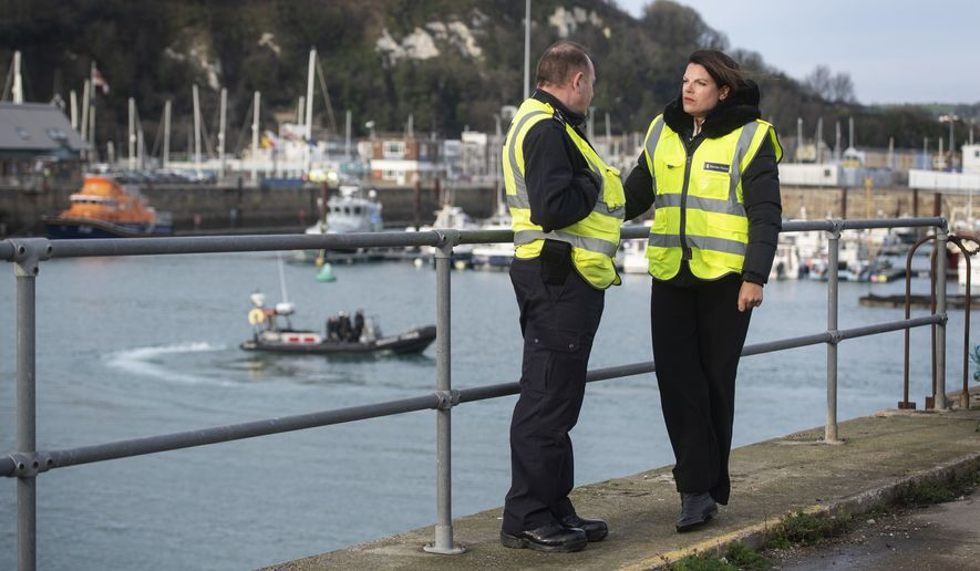 "Britain's Immigration Minister Caroline Nokes talks to a Border Force officer as a Border Force RIB passes in the harbour, in Dover, England, to discuss recent attempts by migrants to reach Britain by small boats, Saturday Dec. 29, 2018.  Home Secretary Sajid Javid is cutting short a family holiday to help deal with the ""major incident"" of a rising number of migrants attempting to cross the English Channel by boat from northern France. (Victoria Jones/PA via AP)"