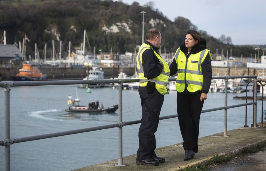 """Britain's Immigration Minister Caroline Nokes talks to a Border Force officer as a Border Force RIB passes in the harbour, in Dover, England, to discuss recent attempts by migrants to reach Britain by small boats, Saturday Dec. 29, 2018.  Home Secretary Sajid Javid is cutting short a family holiday to help deal with the """"major incident"""" of a rising number of migrants attempting to cross the English Channel by boat from northern France. (Victoria Jones/PA via AP)"""
