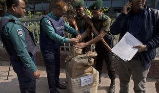 Bangladeshi police personnel seal the voting material at a distribution center before being transported to polling stations on the eve of the general elections in Dhaka, Bangladesh, Saturday, Dec. 29, 2018. As Bangladeshis get set for Sunday's parliamentary elections, there are fears that violence and intimidation could keep many away from the polls, including two opposition candidates who said police had barricaded them inside their homes. (AP Photo/Anupam Nath)