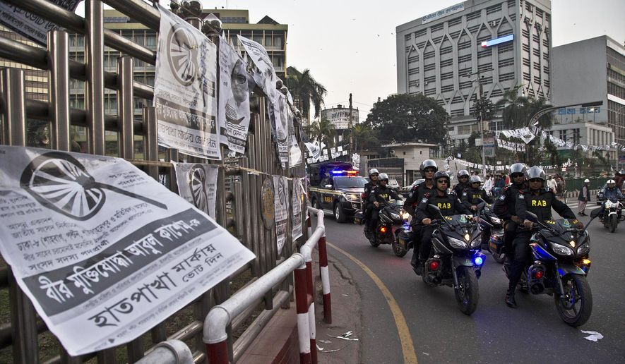 Bangladesh police's elite Rapid Action Battalion (RAB) personnel patrol on motorcycles ahead of the general elections in Dhaka, Bangladesh, Friday, Dec. 28, 2018. Bangladesh Prime Minister Sheikh Hasina is poised to win a record fourth term in Sunday's elections, drumming up support by promising a development bonanza as her critics question if the South Asian nation's tremendous economic success has come at the expense of its already fragile democracy. (AP Photo/Anupam Nath)