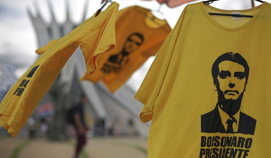 Shirts with the image of Brazil's President-elect Jair Bolsonaro are displayed for sale in front of the Cathedral, in Brasilia, Brazil, Friday, Dec. 28, 2018. The Secretary of Public Security in Brasilia said that they are expecting as many as 500,000 people to attend the ceremony. Brazil's military has deployed anti-aircraft missiles and fighter jets to protect the event from the air. On the ground, more than 3,000 police and military will take to the streets. (AP Photo/Eraldo Peres)