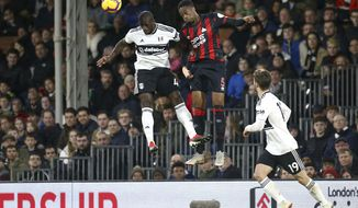 Fulham's Aboubakar Kamara, left, and Huddersfield Town's Terence Kongolo jump for a high ball during their English Premier League soccer match at Craven Cottage in London, Saturday Dec. 29, 2018. (Yui Mok/PA via AP)