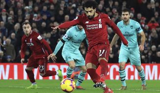 Liverpool's Mohamed Salah scores his side's fourth goal of the game against Arsenal, during their English Premier League soccer match at Anfield Stadium in Liverpool, England, Saturday Dec. 29, 2018. (Peter Byrne/PA via AP)