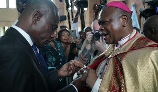 Congolese opposition presidential candidate Martin Fayulu is blessed by Msg. Fridolin Ambongo, the the newly appointed Archbishop of Kinshasa at Notre Dame du Congo cathedral in Kinshasa, Congo, Saturday Dec. 29, 2018. Congolese people are heading to the polls Sunday Dec. 30 for a presidential race plagued by years of delay and persistent rumours of lack of preparation. (AP Photo/Jerome Delay)