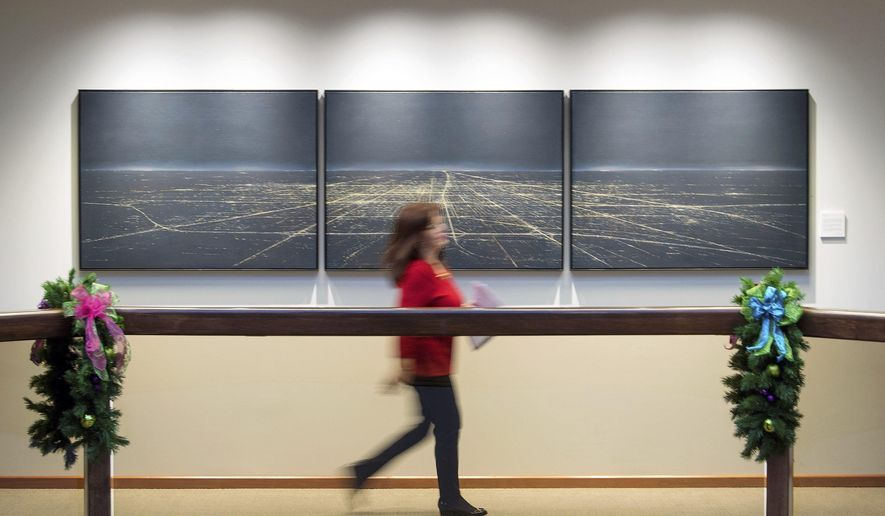 "CORRECTS SPELLING OF PHOTOGRAPHER'S LAST NAME TO HASS INSTEAD OF HSSS - In this Dec. 5, 2018 photo, an employee walks past Eric Nash's oil on canvas piece, ""Jewel of the Prairie,"" part of Busey Wealth Management's recurring exhibition at the company's corporate headquarters In Urbana, Ill. As part of a new initiative to showcase local art, more than 30 pieces now hang upstairs in the public spaces of Busey Wealth Management's corporate headquarters. (Stephen Hass/The News-Gazette via AP )"