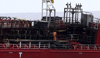 A man on the deck following a fire aboard the Athlos tanker, as it lays aground about 200-yards from the village of Zygi off the south coast of Cyprus, Saturday, Dec. 29, 2018.  Cyprus authorities say five crew members who jumped overboard to avoid a fire aboard the Maltese-flagged oil tanker, have been rescued and taken to hospital.  (AP Photo/Petros Karadjias)