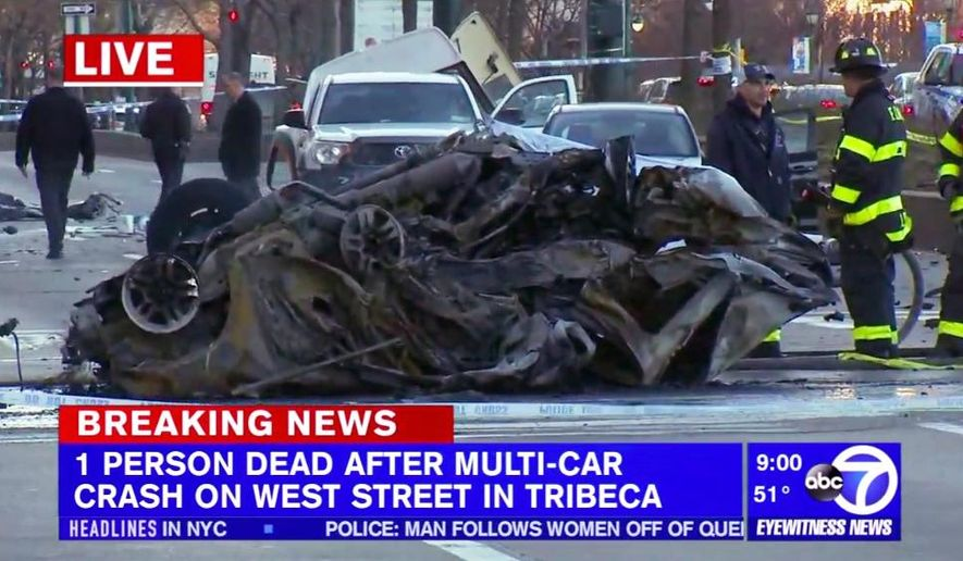 In this image taken from video provided by abc7ny.com, firefighters stand near the charred remains of an automobile that was involved in a fiery four-car crash near the World Trade Center in New York, Saturday, Dec. 29, 2018. (abc7ny.com via AP)