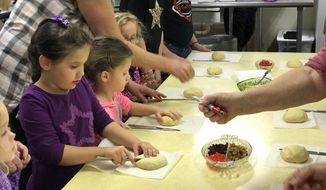 Children and their families making grittibanz in Helvetia, W.Va. for the Feast of Saint Nicholas, Dec. 1, 2018. (Liz McCormick/West Virginia Public Broadcasting via AP)