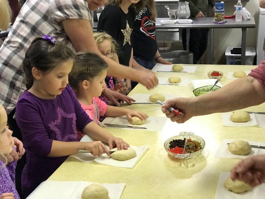 Children and their families making grittibanz in Helvetia, W.Va. for the Feast of Saint Nicholas, Dec. 1, 2018. (Liz McCormick/West Virginia Public Broadcasting via AP)
