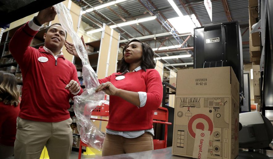 FILE - In this Nov. 16, 2018, file photo, employees demonstrate how air pillow machines work at a packaging station in the backroom of a Target store in Edison, N.J. For many retailers that have lifted pay to attract and keep workers, another challenge has arisen: Making those workers productive enough to justify the larger payouts. (AP Photo/Julio Cortez, File)