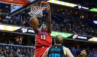 Washington Wizards center Thomas Bryant (13) dunks in front of Charlotte Hornets center Cody Zeller (40 during the second half of an NBA basketball game Saturday, Dec. 29, 2018, in Washington. Washington won 130-126. (AP Photo/Al Drago) **FILE**