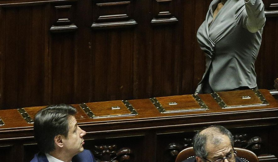 Former lower chamber President Laura Boldrini, top right, shows the Constitution to Italian Premier Giuseppe Conte, left, and Economy Minister Giovanni Tria to protest  during the vote of confidence on the budget law at the Italian lower chamber in Rome, Saturday, Dec. 29, 2018 . (Fabio Frustaci/ANSA via AP)