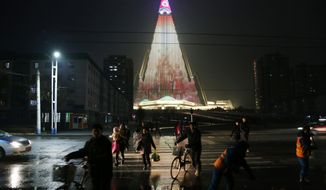 In this Dec. 18, 2018, photo, people cross a street as pyramid-shaped Ryugyong Hotel is seen in the background in Pyongyang, North Korea. Transformed into the backdrop for a gargantuan propaganda display, Pyongyang's yet-to-be-completed 105-story Ryugyong Hotel is once again the talk of North Korea. In a brilliant flip of the script, the uninhabited, pyramid-like building that towers over the North's capital has been festooned with more than 100,000 lights that for several hours every night flash propaganda far and wide. (AP Photo/Dita Alangkara)