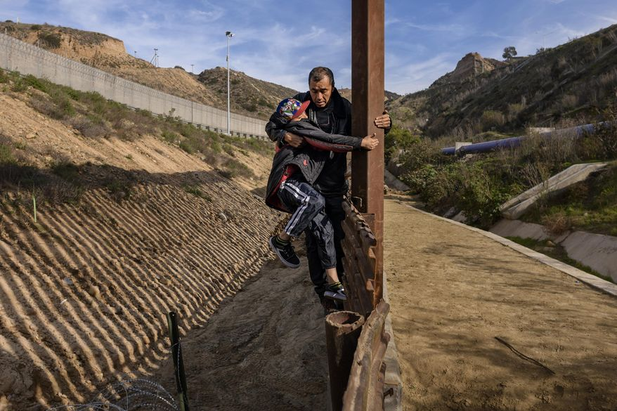 A Honduran migrant grabs his son as they climb the U.S. border fence before jumping into the U.S. to San Diego, Calif., from Tijuana, Mexico, Saturday, Dec. 22, 2018. Discouraged by the long wait to apply for asylum through official ports of entry, many Central American migrants from recent caravans are choosing to cross the U.S. border wall and hand themselves in to border patrol agents. (AP Photo/Daniel Ochoa de Olza)