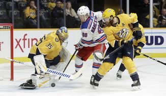 New York Rangers center Vladislav Namestnikov (90), of Russia, and Nashville Predators defenseman Ryan Ellis (4) reach for the rebound after Predators goaltender Pekka Rinne (35), of Finland, blocked a shot in the first period of an NHL hockey game Saturday, Dec. 29, 2018, in Nashville, Tenn. (AP Photo/Mark Humphrey)