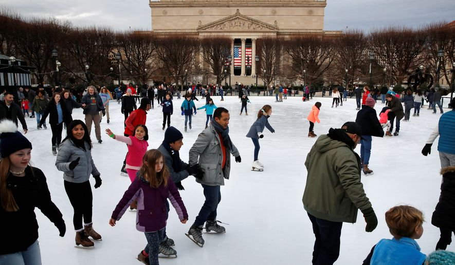 """People skate on the National Gallery of Art Sculpture Garden Ice Rink, Thursday, Dec. 27, 2018, as a partial government shutdown continues in Washington. The museum and the skate rink will be closed to the public after January 2nd as a result of the shutdown if it continues into the new year. Behind the rink is the National Archives, which is closed due to the shutdown. President Donald Trump has vowed to hold the line on his budget demand, telling reporters during his visit to Iraq Wednesday that he'll do """"whatever it takes"""" to get money for border security. The White House and congressional Democrats have been talking but to little effect. (AP Photo/Jacquelyn Martin)"""