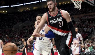 Portland Trail Blazers center Jusuf Nurkic, right, and Philadelphia 76ers guard Ben Simmons, left, go after a ball during the second half of an NBA basketball game in Portland, Ore., Sunday, Dec. 30, 2018. (AP Photo/Steve Dykes)