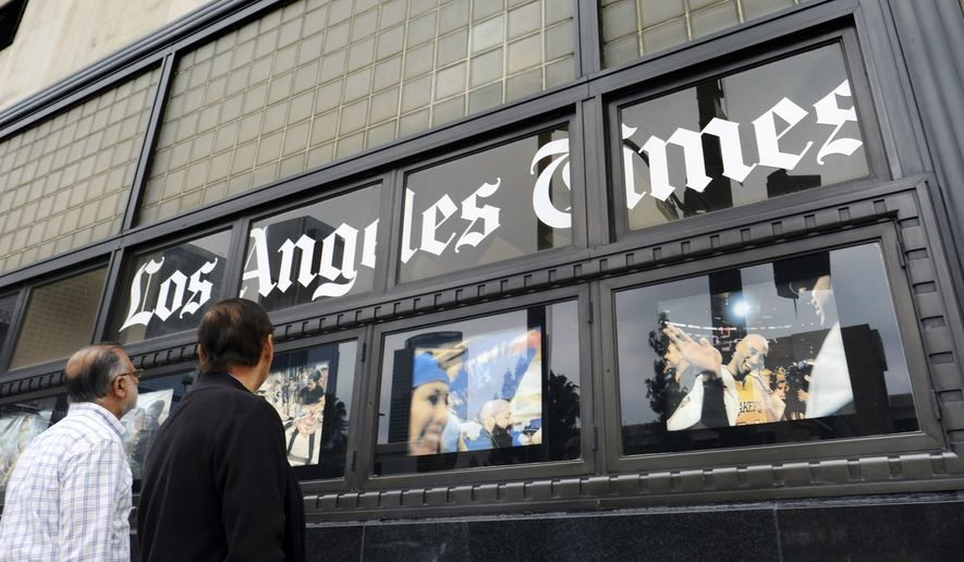 In this May 16, 2016, file photo, pedestrians look at news photos posted outside the Los Angeles Times building in downtown Los Angeles. Biotech billionaire Dr. Patrick Soon-Shion officially took control of the storied newspaper and the San Diego Union-Tribune on June 18, 2018. (AP Photo/Richard Vogel, File)