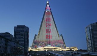 In this Dec. 20, 2018, photo, a propaganda message is displayed on the facade of the pyramid-shaped Ryugyong Hotel in Pyongyang, North Korea. Transformed into the backdrop for a gargantuan propaganda display, the capital city's yet-to-be-completed 105-story Ryugyong Hotel is once again the talk of North Korea. In a brilliant flip of the script, the uninhabited, pyramid-like building that towers over the North's capital has been festooned with more than 100,000 lights that for several hours every night flash propaganda far and wide. (AP Photo/Dita Alangkara)