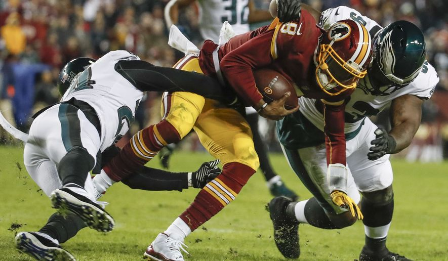 Philadelphia Eagles free safety Corey Graham (24) and defensive tackle Timmy Jernigan (93) haul Washington Redskins quarterback Josh Johnson (8) to the turf during the second half of the NFL football game, Sunday, Dec. 30, 2018 in Landover, Md. (AP Photo/Alex Brandon)
