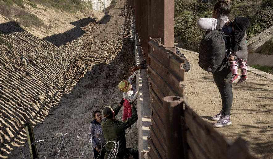 A Border Patrol officer holds a baby as he helps a migrant to go down after they jump the border fence to get into the U.S. side to San Diego, Calif., from Tijuana, Mexico, Saturday, Dec. 29, 2018. Discouraged by the long wait to apply for asylum through official ports of entry, many migrants from recent caravans are choosing to cross the U.S. border wall and hand themselves in to border patrol agents. (AP Photo/Daniel Ochoa de Olza)