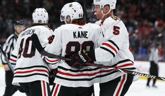 Chicago Blackhawks defenseman Connor Murphy, right, hugs right wing Patrick Kane, who scored against the Colorado Avalanche in overtime of an NHL hockey game Saturday, Dec. 29, 2018, in Denver. The Blackhawks won 3-2. (AP Photo/David Zalubowski)