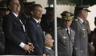 """In this Dec. 1, 2018 photo, Brazil's President-elect Jair Bolsonaro, left, and  Minister of Defense, Gen.Joaquim Silva e Luna, attend a graduation ceremony at the Agulhas Negras Military Academy in Resende, Brazil. """"I am very happy to be in this house that formed me. I owe almost everything in this life to the beloved Brazilian army,"""" said Bolsonaro, during the ceremony. (AP Photo/Leo Correa)"""