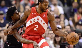 Toronto Raptors forward Kawhi Leonard (2) dribbles the ball as Chicago Bulls forward Justin Holiday (7) defends during first-half NBA basketball game action in Toronto, Ontario, Sunday, Dec. 30, 2018. (Frank Gunn/The Canadian Press via AP)