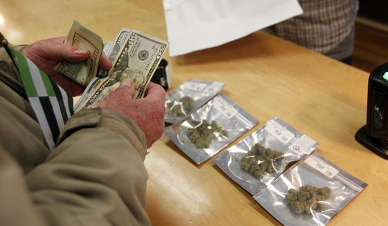 In this Monday, Jan. 1, 2018, file photo, a customer purchases marijuana at the Harborside marijuana dispensary in Oakland, Calif., on the first day that recreational marijuana was sold legally in California. (AP Photo/Mathew Sumner, File)