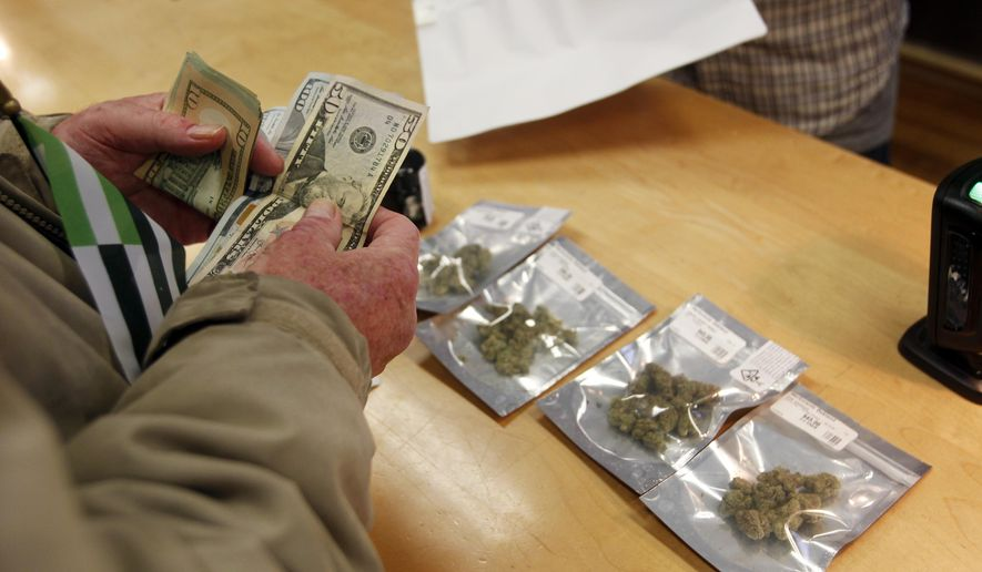 In this Monday, Jan. 1, 2018 file photo, a customer purchases marijuana at the Harborside marijuana dispensary in Oakland, Calif., on the first day that recreational marijuana was sold legally in California. (AP Photo/Mathew Sumner,File) **FILE**