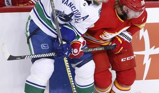 Vancouver Canucks' Alexander Edler, left, from Sweden, battles with Calgary Flames' Elias Lindholm, from Sweden, during the first period of an NHL hockey game Saturday, Dec. 29, 2018, in Calgary, Alberta. (Larry MacDougal/The Canadian Press via AP)