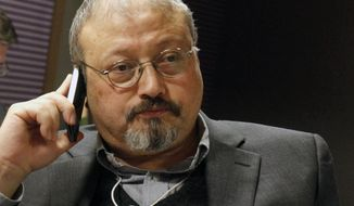 In this Jan. 29, 2011 file photo, Saudi journalist Jamal Khashoggi speaks on his cellphone at the World Economic Forum in Davos, Switzerland. Khashoggi disappeared on Tuesday, Oct. 2, 2018, after visiting his country's consulate in Istanbul, Turkey.  (AP Photo/Virginia Mayo, FILE)