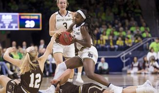 Notre Dame's Jackie Young (5) tries to hang onto the ball as she falls over Lehigh's Gena Grundhoffer (12) and Camryn Buhr (15) in front of Notre Dame's Marina Mabrey (3) during the first half of an NCAA college basketball game Sunday, Dec. 30, 2018, in South Bend, Ind. (AP Photo/Robert Franklin)