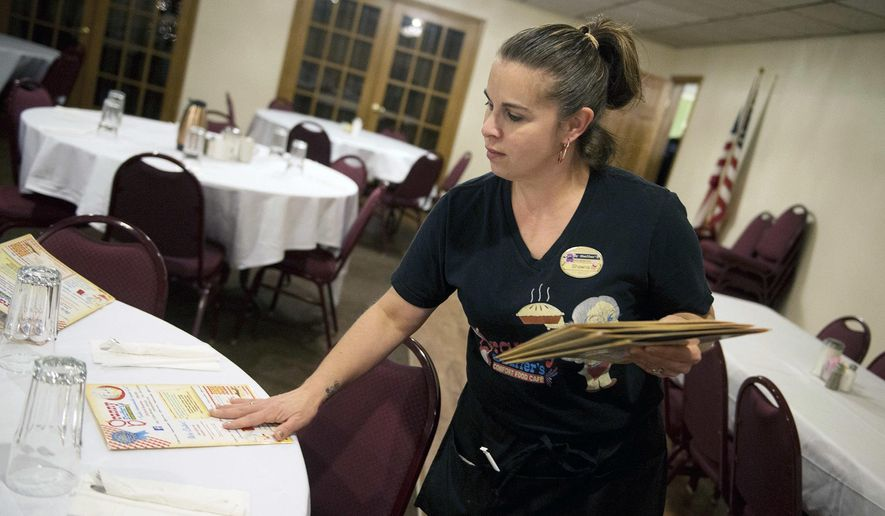 In this Tuesday, Dec. 18, 2018, file photo, Shawna Green, a waitress at Granny Shaffer's, puts out menus for customers at the restaurant in Joplin, Mo. Wages will be increasing for millions of low-income workers across the U.S. as the new year ushers in new laws in numerous states. In Missouri and Arkansas, minimum wages are rising as a result of voter-approved ballot initiatives.  (Roger Nomer/The Joplin Globe via AP)