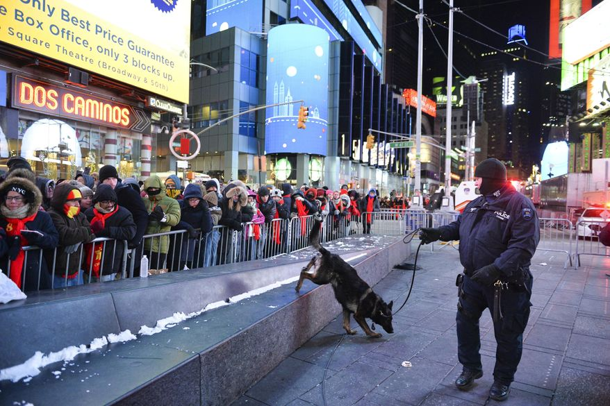 FILE - In this Dec. 31, 2017, file photo, a police K-9 unit patrols in New York's Times Square where crowds were gathered for the annual New Year's Eve celebration. The New York Police Department is adding a drone this year to the security forces it uses to protect the huge crowds celebrating New Year's Eve in the city. (AP Photo/Go Nakamura, File)