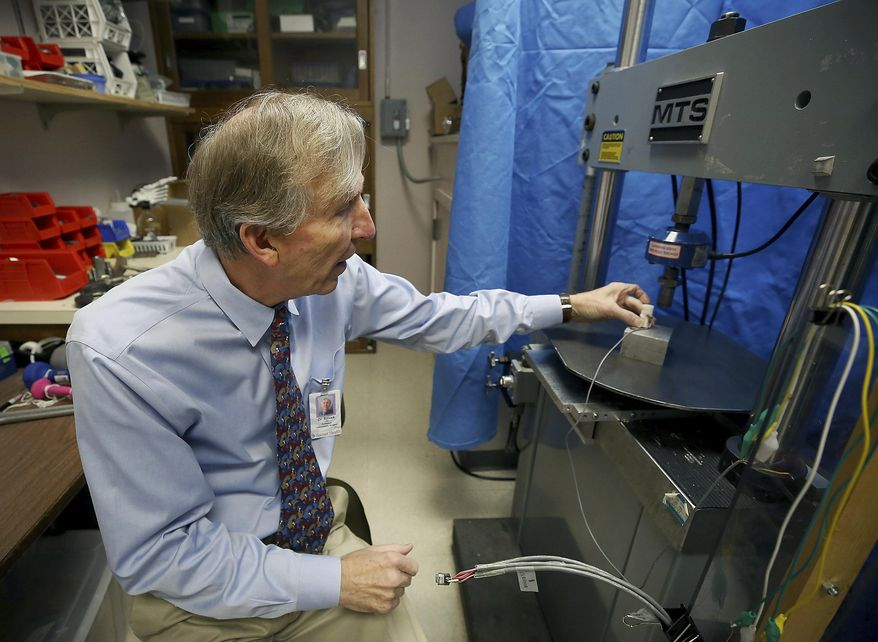 In this Dec. 17, 2018 photo, John Szivek, Rubin chair in orthopedic research professor at the University of Arizona, explains how the scaffold made from a 3-D printer is tested in Tucson, Ariz. Szivek received a $2 million grant from the U.S. Department of Defense to develop technology that could help military personnel recover from bone-shattering injuries using a 3-D printer and adult stem cells. (Mamta Popat /Arizona Daily Star via AP)