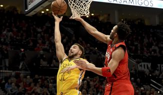 Golden State Warriors guard Klay Thompson, left, drives to the basket on Portland Trail Blazers guard Evan Turner, right, during the first half of an NBA basketball game in Portland, Ore., Saturday, Dec. 29, 2018. (AP Photo/Steve Dykes)