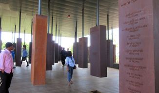 FILE - In this April 28, 2018, file photo, visitors look at markers bearing the names of lynching victims at the National Memorial for Peace and Justice in Montgomery, Ala. It's opening was one of the top stories in Alabama in 2018. (AP Photo/Beth J. Harpaz, File)
