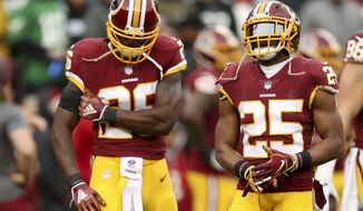 Washington Redskins running back Adrian Peterson, left, and Washington Redskins running back Chris Thompson, right, during warmups before an NFL football game against the Philadelphia Eagles, Sunday, Dec. 30, 2018, in Landover, Md. The Eagles defeated the Redskins 24-0. (AP Photo/Andrew Harnik)
