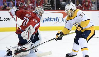 Washington Capitals goaltender Braden Holtby (70) stops Nashville Predators right wing Viktor Arvidsson (33), of Sweden, during the second period of an NHL hockey game, Monday, Dec. 31, 2018, in Washington. (AP Photo/Nick Wass)